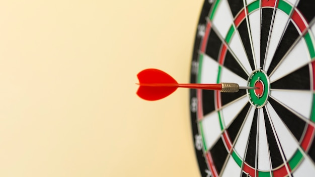 Front view of dart in bull's-eye on defocused board