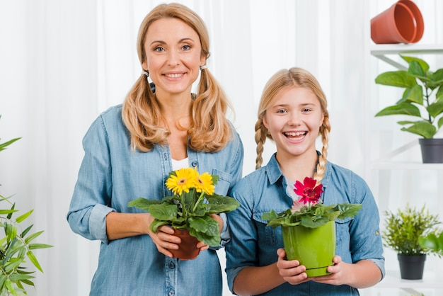 Front view daughter and mom holding flowers pot