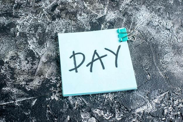 Vista frontale giorno nota scritta su adesivo blu su superficie grigia lavoro colore squadra foto ufficio lavoro scuola college blocco note business
