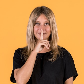 Front view of deaf woman with silent gesture in front of yellow background