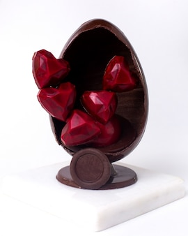 Front view decorated chocolate egg with chocolate red candies in the shape of a heart inside on stand