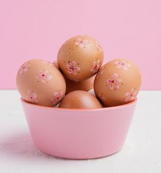 Vista frontale delle uova di pasqua decorate nella ciotola