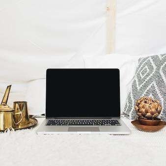 正面には、空白の画面のラップトップを備えたホーム オフィスのデスク ワークスペースが飾られています。モダンなスタイルのビジネス コンセプト