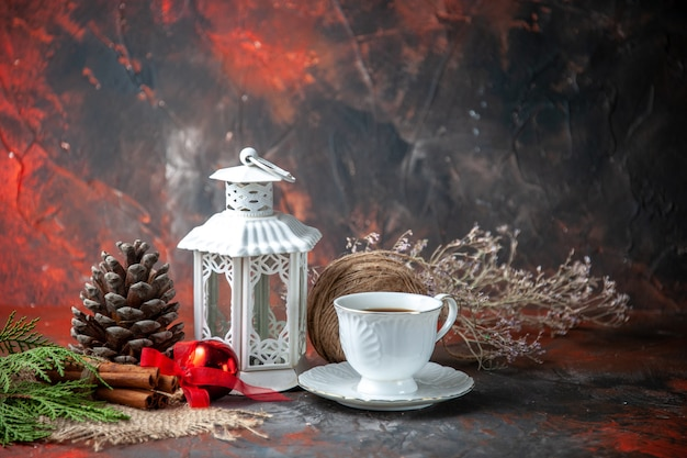Front view of decoration accessories conifer cone a ball of rope and fir brances cinnamon limes a cup of tea on dark background