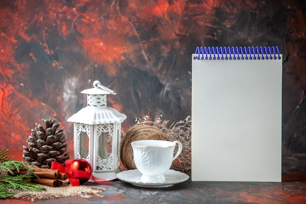 Front view of decoration accessories conifer cone a ball of rope and fir brances cinnamon limes a cup of tea and notebook on dark background