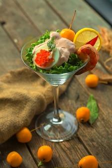 Antipasto decorativo vista frontale in un bicchiere con salsa di gamberi una fetta di caviale lemonnd