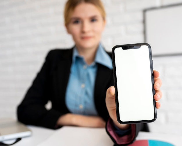Front view of defocused businesswoman holding smartphone in the office