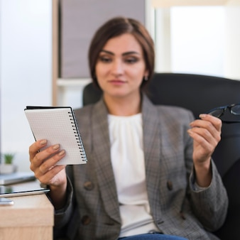 Front view of defocused businesswoman looking at notebook