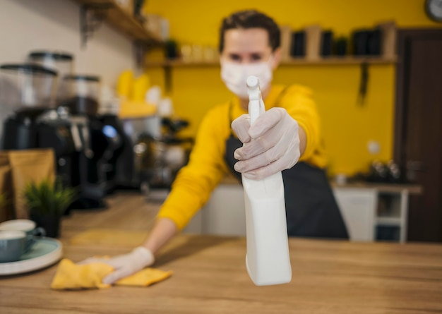 Front view of defocused female barista with medical mask