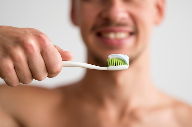 Front view of defocused man holding toothbrush with toothpaste on it