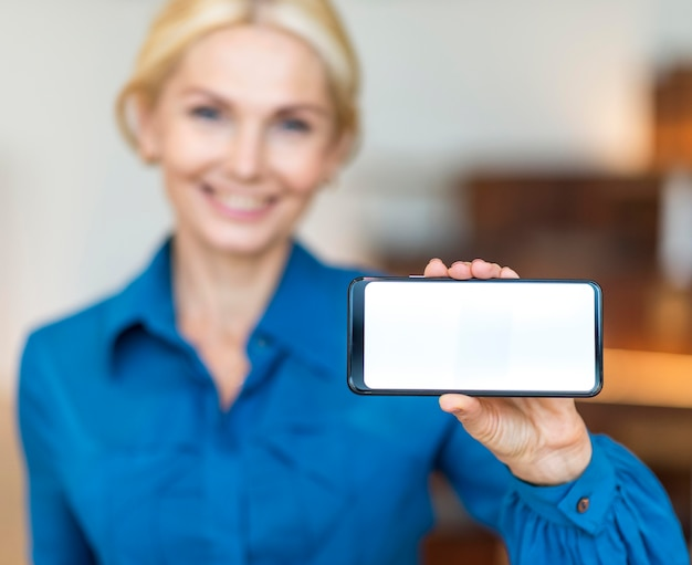 Front view of defocused smiley business woman holding smartphone