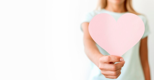Front view of defocused woman holding heart shape with copy space