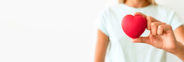 Front view of defocused woman holding heart shape