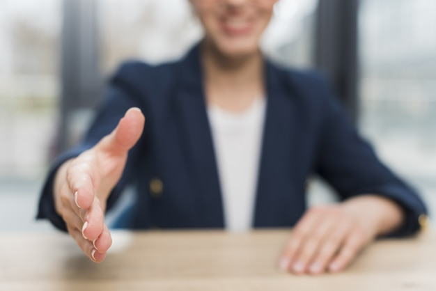 Front view of defocused woman offering hand shake after being hired