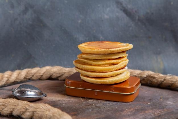 Vista frontale di deliziosi muffin gustosi rotondi formati con corde sulla superficie grigia