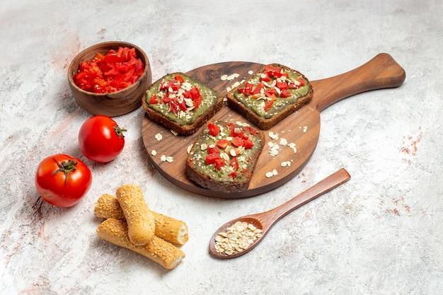 正面図白いスペースに新鮮な赤いトマトとおいしいアボカドサンドイッチ