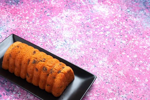 Вкусный испеченный торт вид спереди внутри черной формы для торта на розовом столе. Бесплатные Фотографии