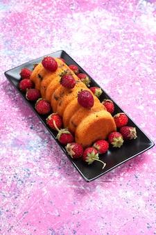Вид спереди восхитительный испеченный торт внутри черной формы для торта со свежей красной клубникой на розовом столе.