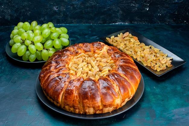 Вид спереди вкусный запеченный торт с изюмом и свежим зеленым виноградом на темно-синей поверхности торт пирог сахарное сладкое бисквитное тесто