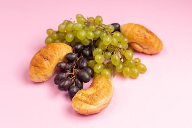 ピンクの机の上の新鮮な黒と緑のブドウと一緒にフルーツが入った正面のおいしい焼きたてのクロワッサン