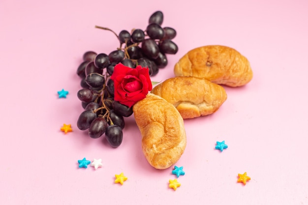 ピンクの机の上に新鮮な黒ブドウと一緒にフルーツが詰まったおいしい焼きたてのクロワッサンの正面図
