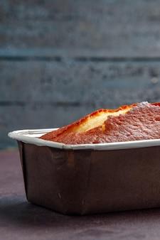 Vista frontale deliziosa torta al forno torta dolce per il tè su sfondo scuro torta al tè biscotto torta dolce pasta di zucchero