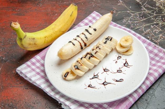 正面図暗い背景のプレートの内側にスライスされた断片を持つおいしいバナナ果樹の写真甘い味