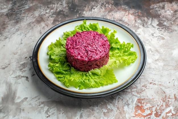 Vista frontale deliziosa insalata di barbabietole a forma rotonda su insalata verde su sfondo chiaro