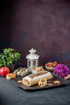 正面図暗い背景にナッツとおいしいビスケットロールパイクッキーケーキデザート茶砂糖生地甘い花