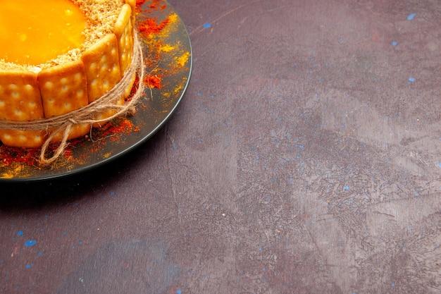 正面図ダークデスクケーキビスケットパイシュガースイートクッキーにクリームとクラッカークッキーとおいしい明るいケーキ