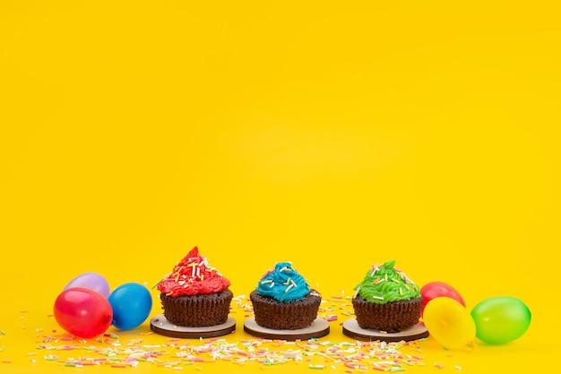 Una vista frontale deliziosi brownies a base di cioccolato insieme a caramelle di colore giallo, caramelle torta biscotto