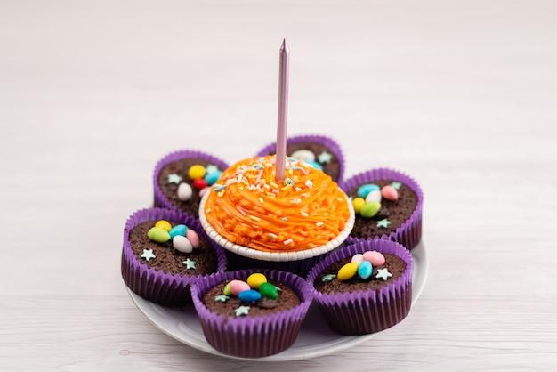 Una vista frontale deliziosi brownies all'interno di forme viola con caramelle colorate su bianco, caramelle color caramelle