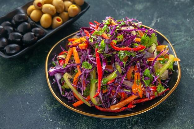 Вид спереди вкусный салат из капусты с перцем внутри тарелки на темном фоне