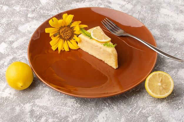 Front view of delicious cake slice with lemon inside brown plate on the light surface