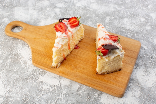 Front view of delicious cake slices with chocolate cream and strawberry on the light surface