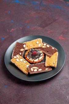 어두운 공간에 견과류와 작은 비스킷이있는 전면보기 맛있는 케이크 조각