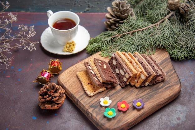 Fette di torta deliziose vista frontale con noci e cacao nello spazio buio