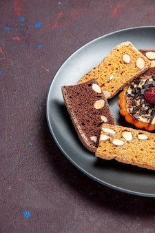 Fette di torta deliziose vista frontale con noci e biscotto su spazio buio