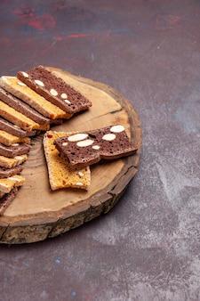 Вид спереди вкусные кусочки торта с орехами на темном столе чай сахарное печенье бисквит сладкий пирог торт