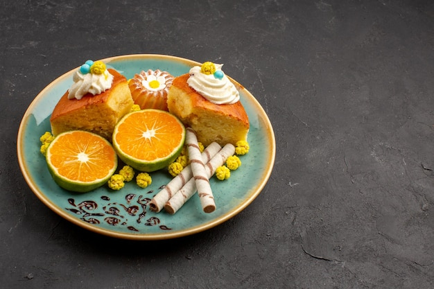 Front view delicious cake slices with pipe cookies and sliced tangerines on dark space