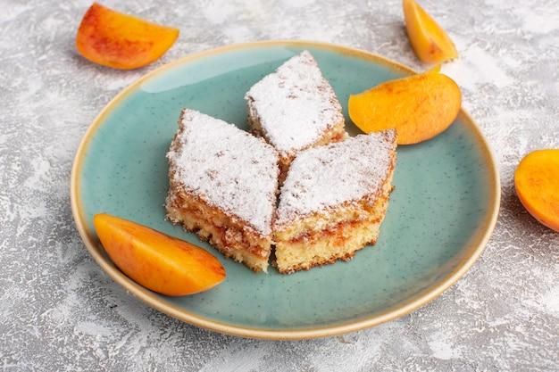Вид спереди вкусные кусочки торта с сахарной пудрой и свежими персиками внутри тарелки на столе, выпечка из сладкого бисквита с сахаром