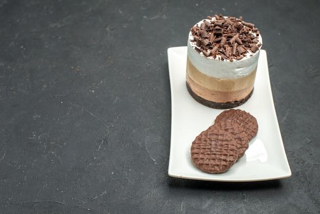 Vista frontale deliziosa torta con cioccolato e biscotti su piatto rettangolare bianco su spazio libero scuro