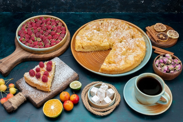 Вид спереди вкусный торт с чаем и фруктами на темно-синем столе пирог торт сладкое печенье сахар