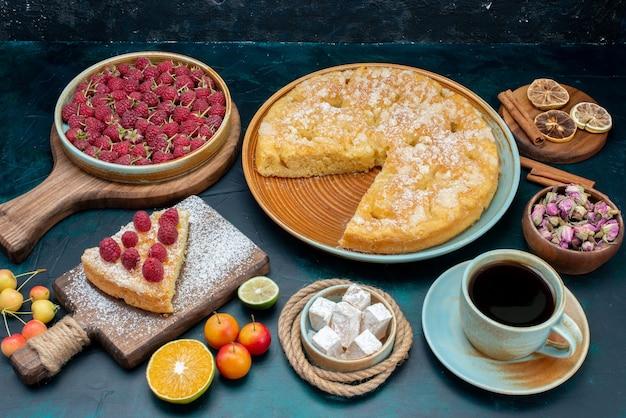 Vista frontale deliziosa torta con tè e frutta sullo zucchero di biscotto dolce torta scrivania blu scuro