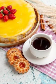 Вид спереди вкусный торт с желтым сиропом, свежая красная клубника и чашка чая на синей поверхности