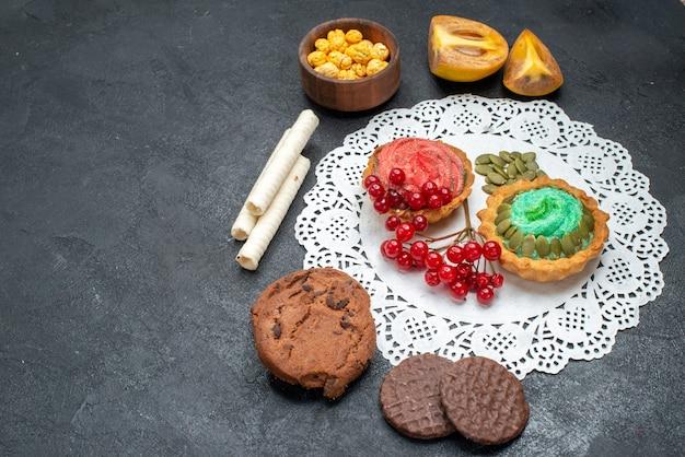 Vista frontale deliziose torte con biscotti e frutta su sfondo scuro