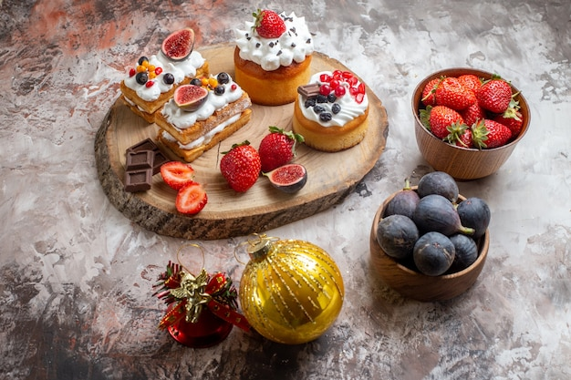 Front view delicious cakes with fresh fruits on light background christmas cake dessert biscuit color