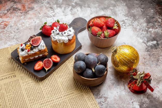 Vista frontale deliziose torte con frutta fresca su sfondo chiaro torta di natale dessert biscotto di colore