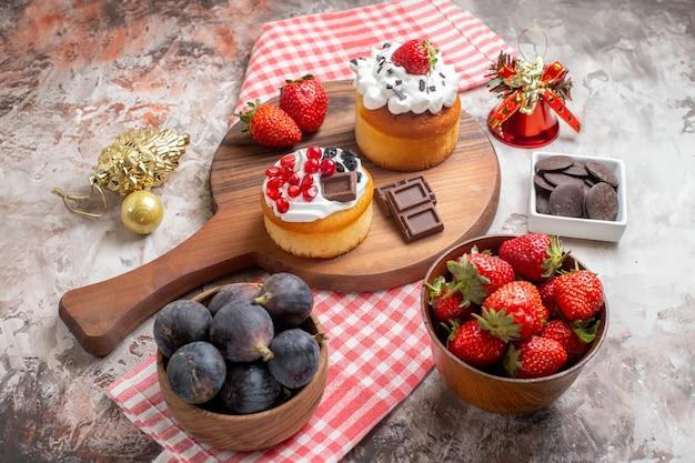 明るい背景に新鮮な果物とおいしいケーキを正面から見るビスケットの甘いケーキのデザートの色