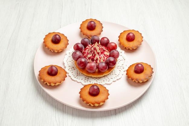 正面図白い背景の上のブドウとおいしいケーキ